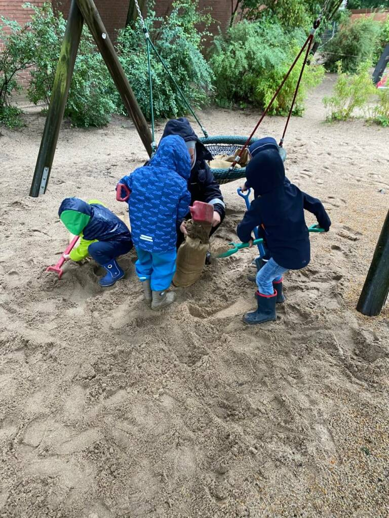Kindergartenkinder in Dinslaken befüllen einen Sandsack