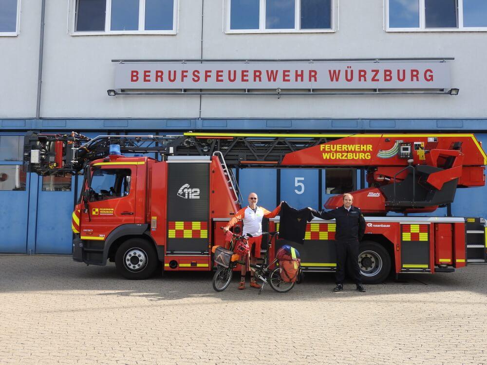 Brandoberinspektor Christoph Hartmann (rechts) überreicht dem ehemaligen Feuerwehrmann Jörg Richter ein Poloshirt, dass ihn an seine Radtour vom Mittelmeer über die Alpen nach München erinnern soll.